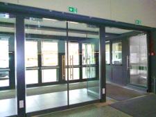 Glas-Windfang, zweiflügelige Türen mit Obentürschließer in Ganzglas-Konstruktion.