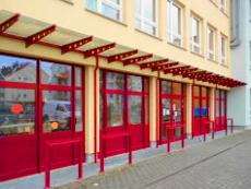 Außentüranlage mit seitlichen Fensteranlagen, Glas-Vordach auf der gesamten Länge.