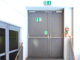 Fluchttüre mit Panikstangengriffen, Fluchttürsteuerung verriegelt um unbefugte Benutzung zu verhindern.