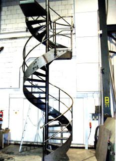Spindeltreppe aus Stahl, mehrgeschossig, mit Austrittspodest und Zwischenpodest.