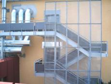 Außentreppenanlage aus Stahl mit Verblendung aus Gitterrost, Zwischenpodest, mehrstöckig.