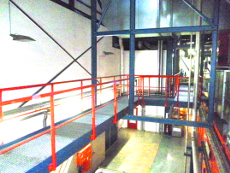 Abgehängter Industrielaufsteg mit Gitterrostbelag, Geländer, Handlauf, Knieleiste, Fußleiste.