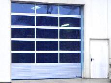 Industrie-Sektionaltor, Motor-Antrieb, unten Lamellensockel, oben großflächige Verglasung.