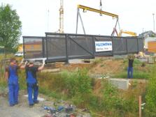 Fußgängersteg bzw. -brücke aus Stahl über einen Bach, Montage, Betonfundamente.