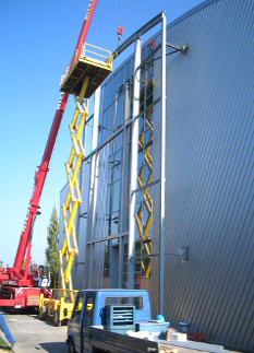 Fassadenvorbau mit isolierten Aluminiumtrapezblechen und Pfosten-Riegel-Glasfassade.