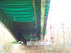 Instandsetzungsarbeiten einer Stahlstraßenbrücke mit einem Brückenuntersichtgerät.