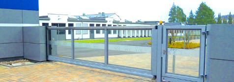 Außenschiebetor mit automatischem Torantrieb, Sicherheitseinrichtungen, Tor freitragend, also ohne Laufschiene, Glasfüllung, Alu-Paneele verkleidete Konstruktion mit integriertem Lichtband.